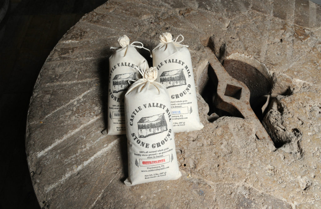 Some of the products of Castle Valley Mill, owned by Mark and Fran Fischer, sitting on an old mill stone. (Clem Murray/Staff Photographer)