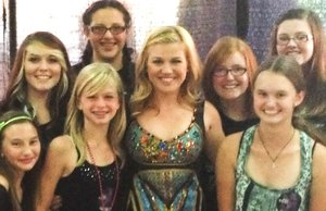 Kelly Clarkson poses with kids from the Delco Let There Be Rock School before her Susquehanna Bank Center concert.