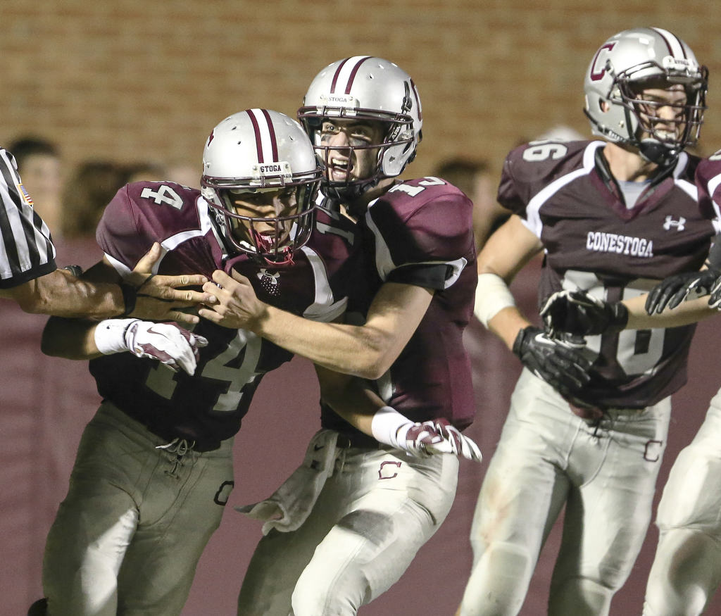 Conestoga´s Martin Dorsey (left) celebrates with quarterback Tim Miller and teammates after scoring his third touchdown against Ridley earlier this month. (Steven M. Falk/Staff Photographer)