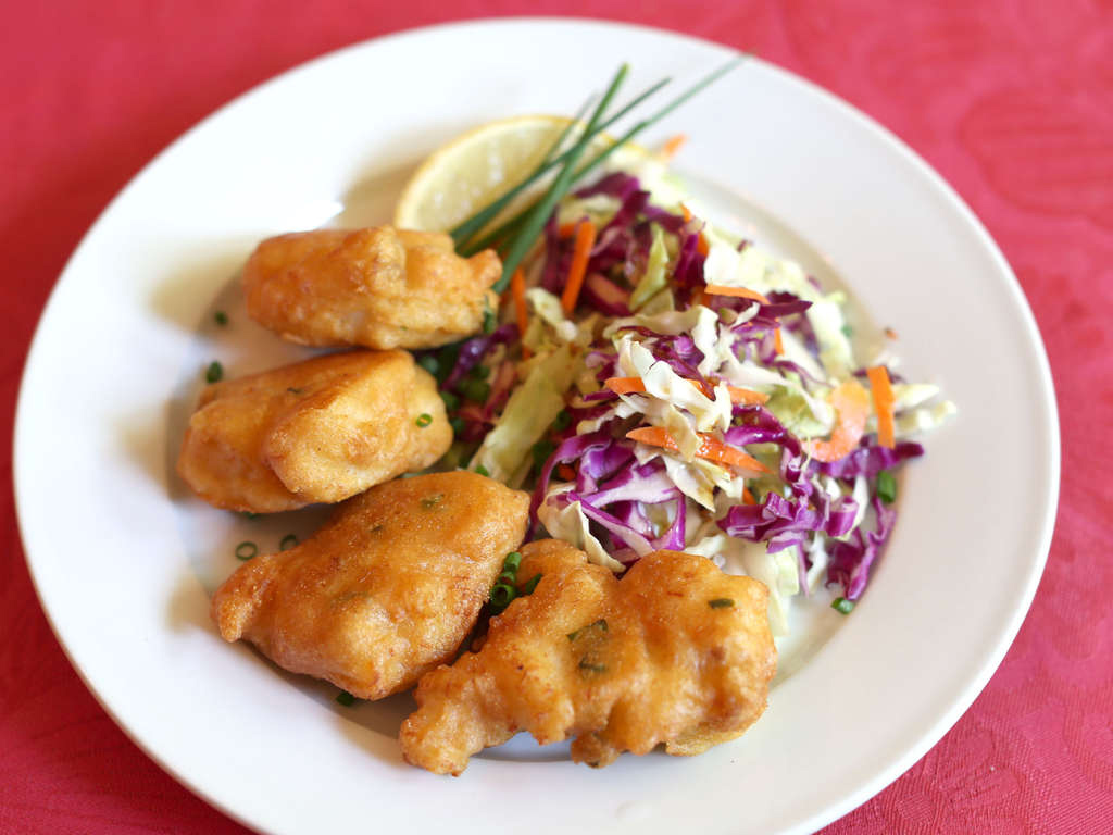 Spicy beer-battered fish fritters - made with cornmeal, scallions, cod, and, of course, beer - are served with a festive, colorful cole slaw.