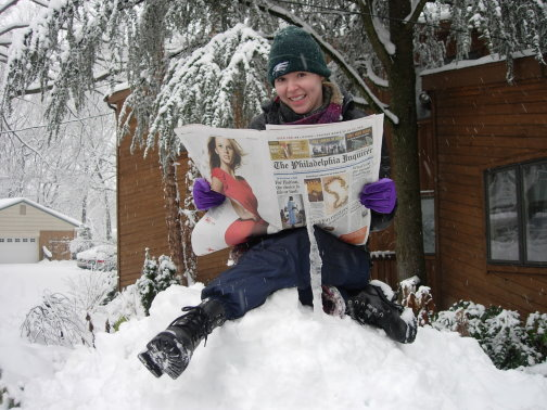 Author Diana Rodriguez Wallach reading the Inquirer on a homemade snowdrift in Wallingford on her birthday.
