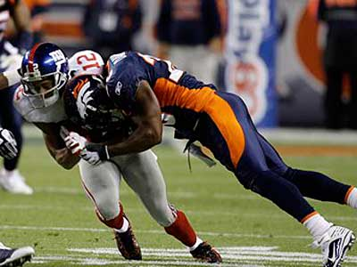 New York Giants wide receiver Steve Smith is tackled by Denver Broncos safety Brian Dawkins during the first quarter of an NFL football game in Denver. (AP Photo/Darron Cummings)