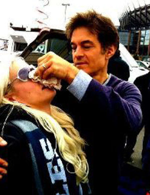 Dr. Mehmet Oz pinches singer Erika Schiff´s bloody nose before she serenaded him Sunday before the Eagles game.