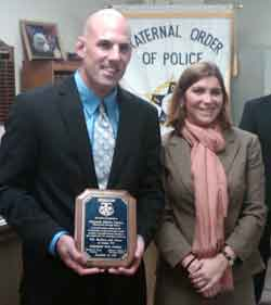 Phoenixville Sgt. Robert Sutton shows off the plaque he was presented by Assistant District Attorney Marilyn Seide (right), who successfully prosecuted the rapist whom Sutton apprehended.