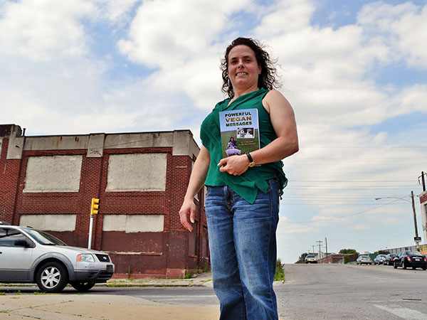 """Anne Dinshah stands holding her new book """"Powerful Vegan Messages"""" in front of the now closed Cross Bros. Meat Packing Co. on Monday, June 30, 2014.  (C.F. Sanchez / Staff Photographer)"""