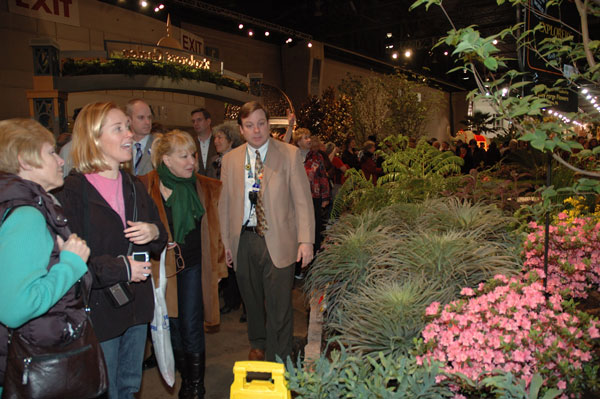 Bette Midler alongside fellow admirers at the Philadelphia International Flower Show with show designer Sam Lemheney (tan coat) and Drew Becher (who stands in background) the incoming Pennsylvania Horticultural Society president.