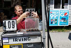 Convenience story owner Floyd Bisson lowering the price of regular gas at the pumps in front of his store in Phippsburg, Maine, on  June 27.
