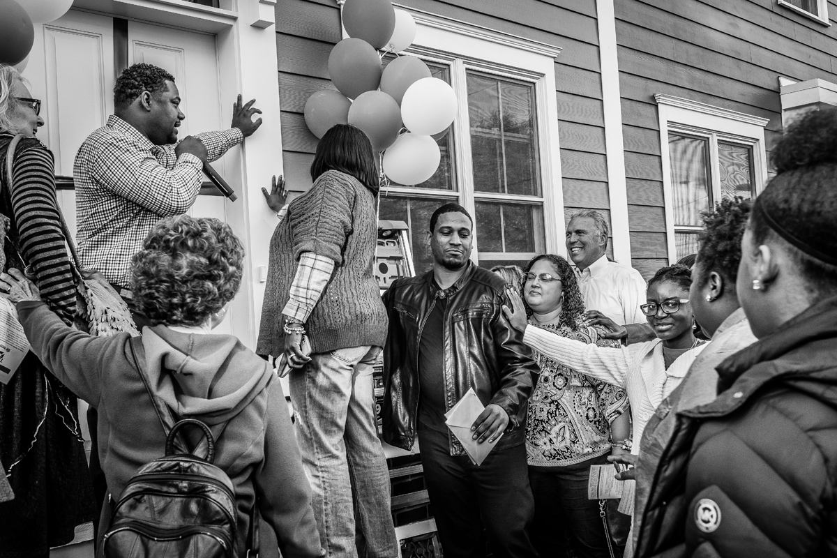 William Harding (center, in leather jacket) listens to his brother David (with mic) lead a prayer at Saturday's dedication of William's new Habitat for Humanity home.