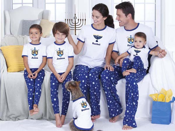 This photo provided by Vermont Teddy Bear Company shows the Chanukah Pajamas for the Whole Family by PajamaGram, featuring short-sleeved ringer tees with a menorah on the front paired with full-length pants with an all-over star print. New pajamas are a holiday tradition in many families.  (AP Photo/Vermont Teddy Bear Company)