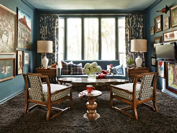 This publicity photo provided by Brian Patrick Flynn shows a living room designed by Brian Patrick Flynn, where he uses a colorful red, white and blue palette balanced by wood tones and muted browns to create a rich, layered look in this weekend home. (AP Photo/Brian Patrick Flynn, Daniel Collopy)