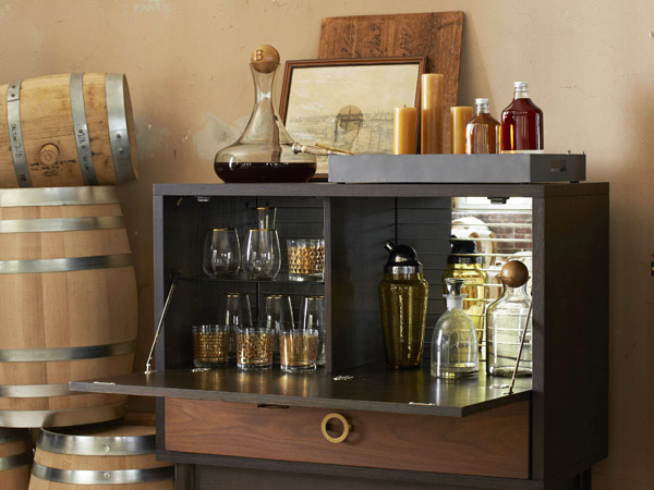This photo provided by West Elm shows The Dodson bar which has flip down shelves and lots of storage. Bar carts are a great way to set up a bar in a small space.  Some have wheels or casters so the carts can be rolled to one side when not in use. (AP Photo/West Elm)