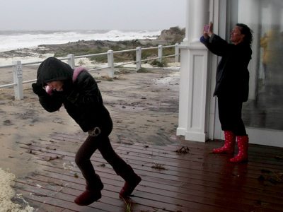 Madison Maher, left, runs out into the rain and wind while her mother, Susan Sorenson, takes a picture of the rough surf in Sea Bright, N.J., Monday, Oct. 29, 2012. Hurricane Sandy continued on its path Monday, as the storm forced the shutdown of mass transit, schools and financial markets, sending coastal residents fleeing, and threatening a dangerous mix of high winds and soaking rain. (AP Photo/Seth Wenig)