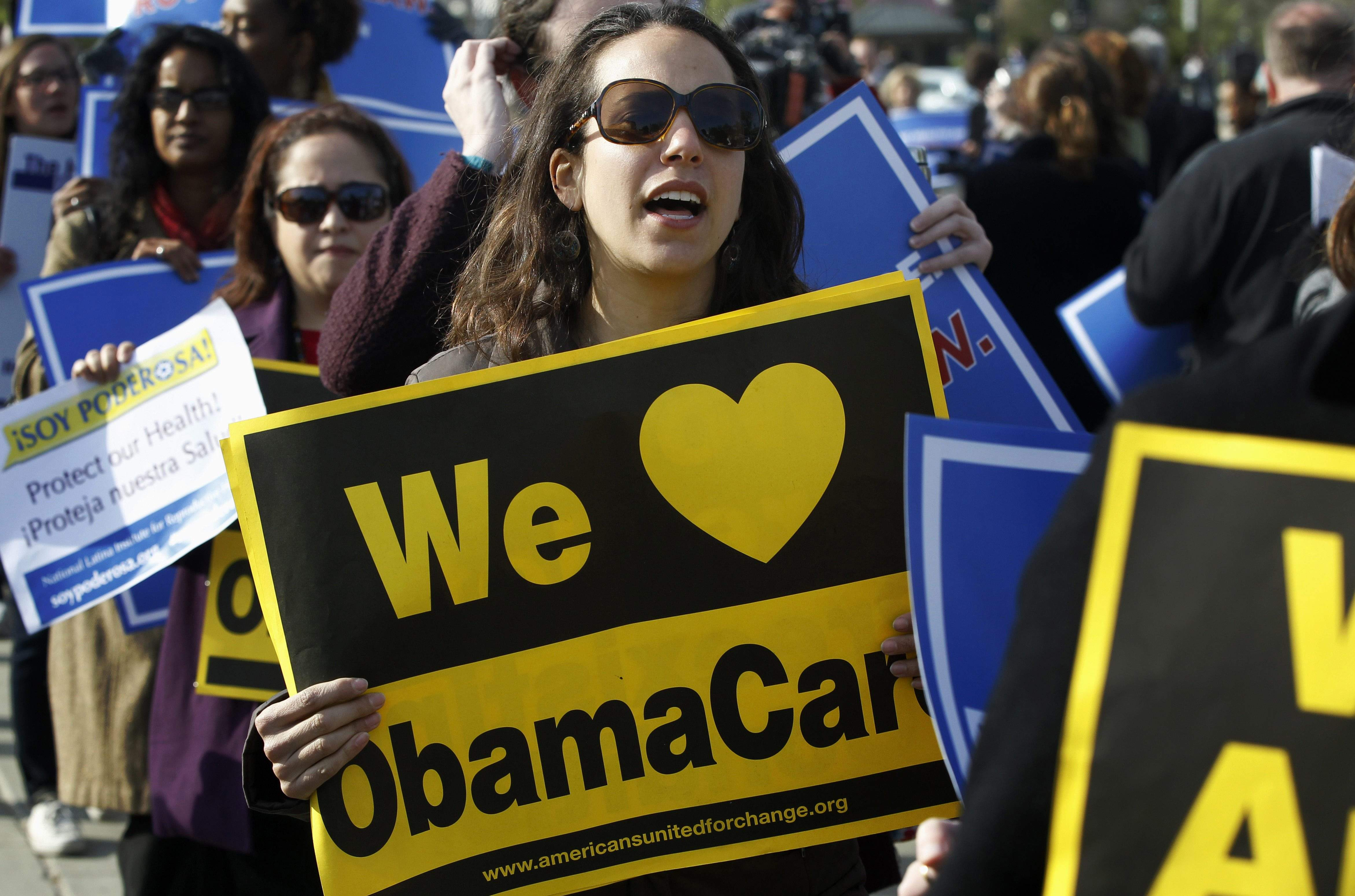 Supporters of the Affordable Care Act  stood in front of the Supreme Court in Washington on Wednesday, the final day of arguments regarding the health-care law signed by President Obama. The justices are reviewing the constitutionality of the 2,700-page law.  CHARLES DHARAPAK / Associated Press