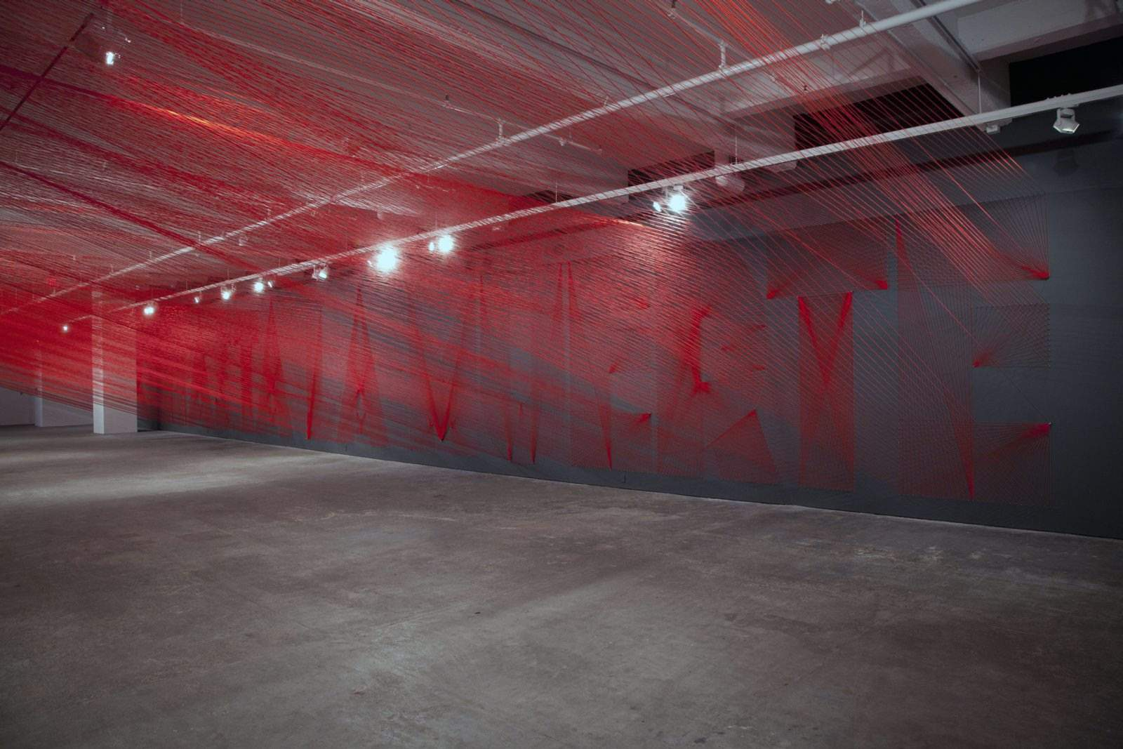 "Pae White´s ""Summer XX."" The phrase ""Hasta la muerte,"" ""until death,"" is spelled out on a wall in yarn. The room is so suffused with brilliant red one feels surrounded in a mist of it. CARLOS AVENDAÑO"