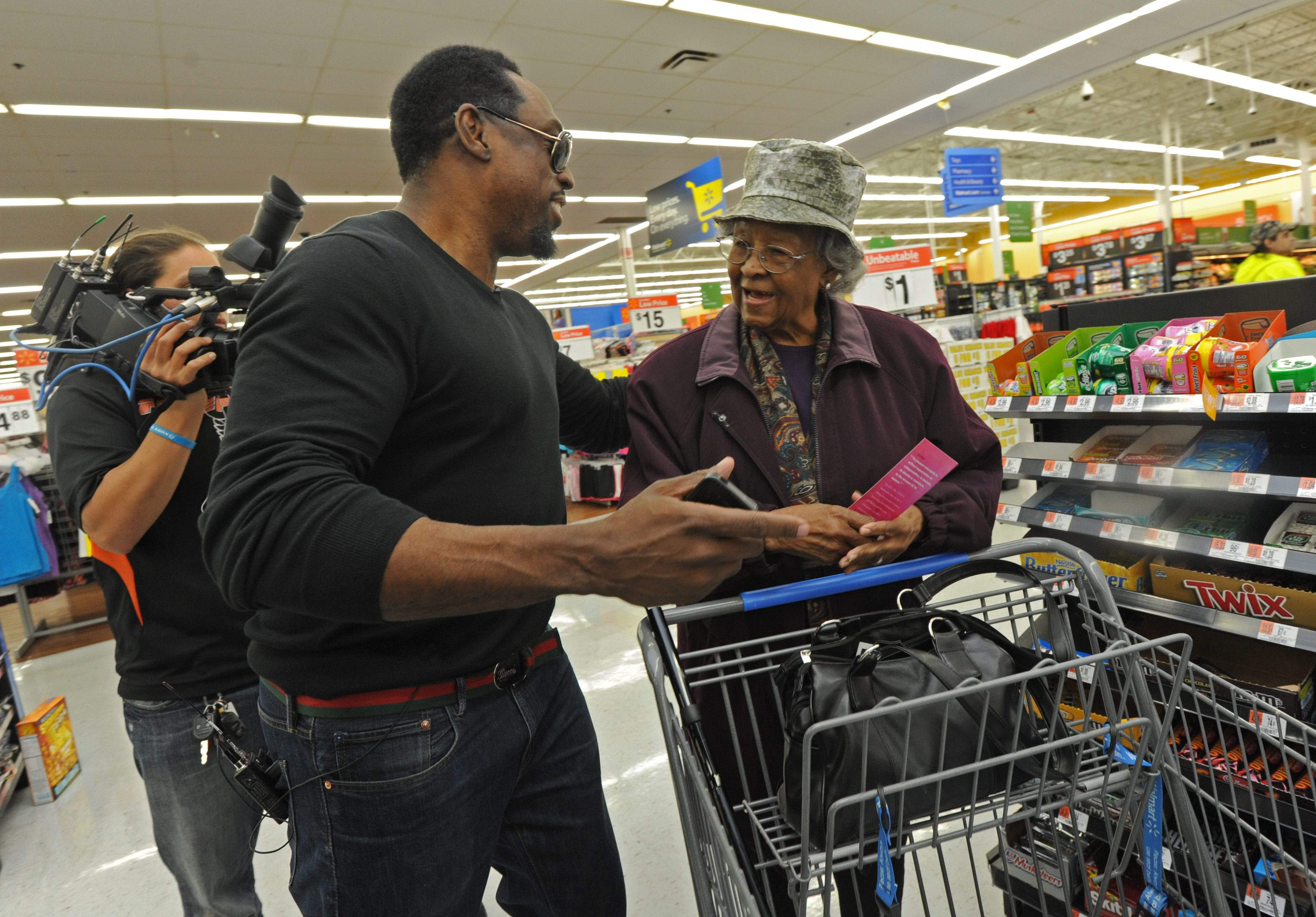 Keven Parker, whose Spread the Love Foundation helps others, surprises Geneva Dawson at a Wal-Mart with the news that he'll be paying for what's in her shopping cart.   APRIL SAUL / Staff Photographer