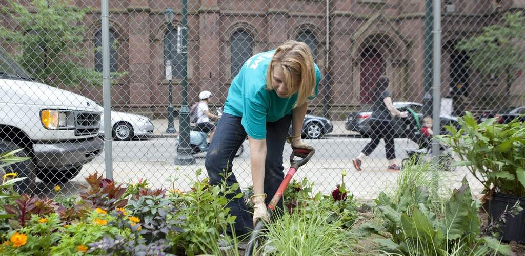 In a vacant lot located diagonally from Rittenhouse Square at 19th and Walnut, Susannah Henderson, a volunteer from Shire Pharmaceuticals, plants in the pop-up garden. Ed Hille / Staff Photographer