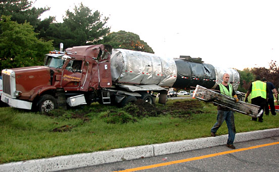 Highway workers clean up debris from an overturned tanker truck that failed to negotiate the New Jersey Route 130 South exit ramp to Route 322 West early this morning. The ramp was closed for several hours during the morning rush hour as the truck was righted.  (Clem Murray / Staff Photographer)