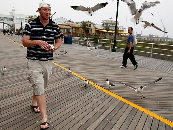 Jeff Thompson, of York, Pa., is followed by a flock of seagulls as he tries to eat funnel cake on the boardwalk in Atlantic City, NJ on May 23, 2013.  ( DAVID MAIALETTI / Staff Photographer )