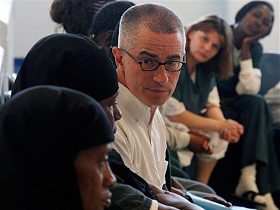 FILE - In this Tuesday, Aug. 2, 2011 file photo, former New Jersey Gov. James McGreevey, center, listens as an inmate speaks to a gathering of women inmates at Integrity House, a transitional housing and residential treatment area for women incarcerated at the Hudson County Correctional Center, in Kearney, N.J. The jailhouse treatment program where McGreevey works has earned a spot at the Sundance Film Festival and accolades from the U.S. Justice Department. McGreevey is spiritual counselor to 40 women in a pilot program to keep them from returning to jail. The Justice Department cites the program as one of two top re-entry efforts nationwide. The struggles of the women as well as McGreevey´s own admission that he is gay and resignation as governor are the subject of a documentary showing at the Sundance Film Festival in January.  (AP Photo/Mel Evans, File)