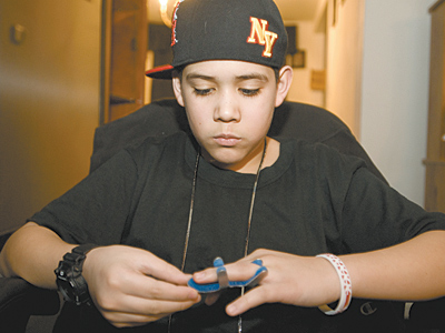 Jonathan Rojas looks at the finger broken last fall during a fight at Woodrow Wilson Middle School in the Northeast. The school didn´t call police until the day after the assault, which angers Rojas´ mother. (Ron Tarver/Staff)