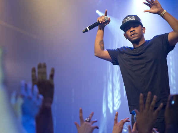 Kendrick Lamar performing in front of an enthusiastic festival crowd.