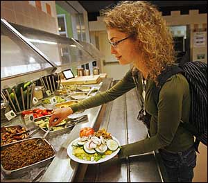 Kristin Zuhone, 18, of New Jersey spoons some Curried Red Bean salad onto her plate of vegetables.