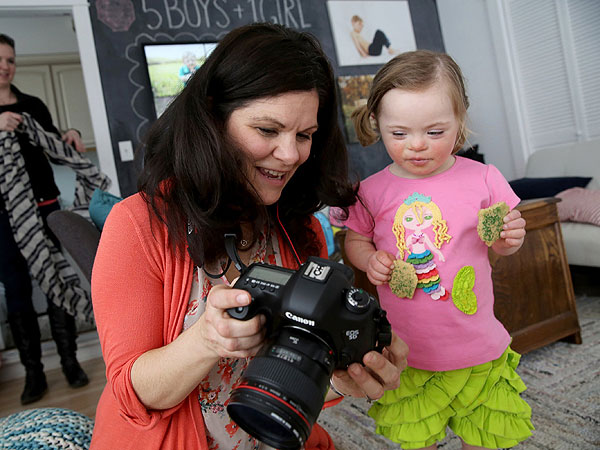"Katie Driscoll, center, shows daughter Grace, 4, who has Down syndrome, photos taken of her at her Palos Park, Ill., home studio for ""Lemon Loves Lime"" children´s clothing designer, March 20, 2014. (Antonio Perez/Chicago Tribune/MCT)"