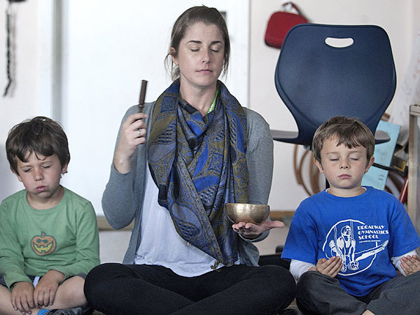 Kindergarten teacher Erica Eihl, center, leads the meditation while Lucas Gold, left, and Husam Arab concentrate on deep breathing at Citizens of the World Mar Vista in Culver City, Calif., on February 11, 2014. Principal Alison Kerr implemented meditation practices four months ago. (Cheryl A. Guerrero/Los Angeles Times/MCT)