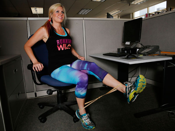 Kristi Dear, a personal trainer, demonstrates exercises that can be done in the workplace. (Andy Jacobsohn/Dallas Morning News/MCT)