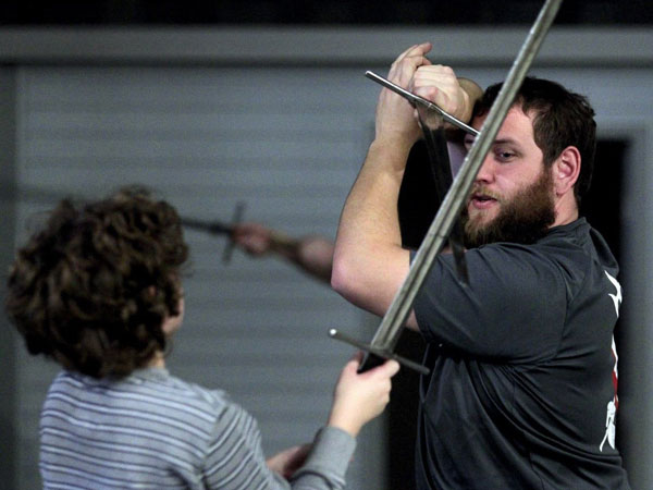 Jeremiah Backhuas, right, works with Elan Graupe, 12, at Sword Camp in Jackson, Wisc. The camp teaches basics of historical fencing and sword play. (Kristyna Wentz-Graff/Milwaukee Journal Sentinel/MCT)