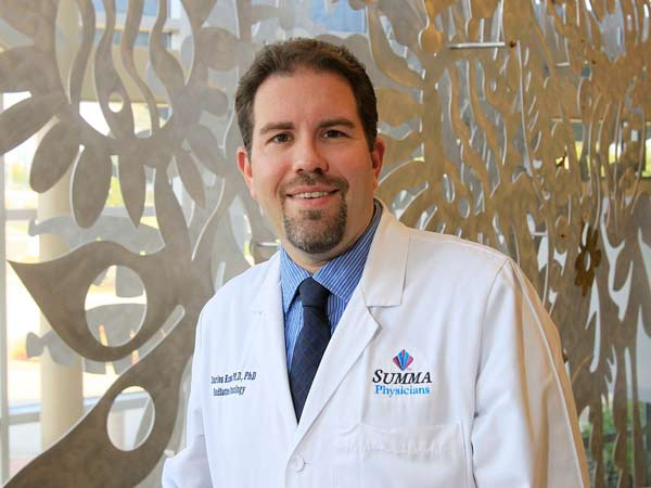 Dr. Charles A. Kunos, a radiation oncologist at the Summa Cooper Cancer Center, stands in front of Don Drumm sculpture at the center´s entrance July 31, 2014 in Akron, Ohio. Dr. Kunos is leading a national clinical trial that may help cure more cases of cervical cancer. (Karen Schiely/Akron Beacon Journal/MCT)