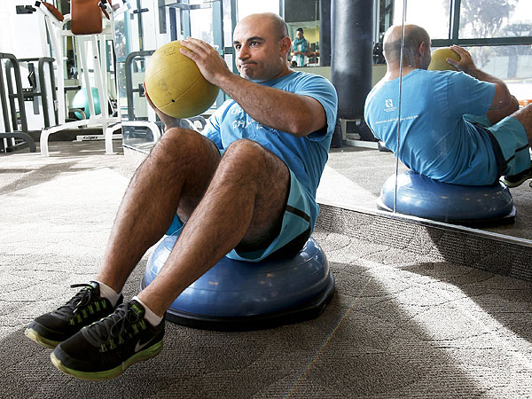 Orthopedic surgeon Hooman Melamed demonstrates crunches using a ball at Spectrum in Santa Monica, Calif., on December 17, 2013. (Anne Cusack/Los Angeles Times/MCT)