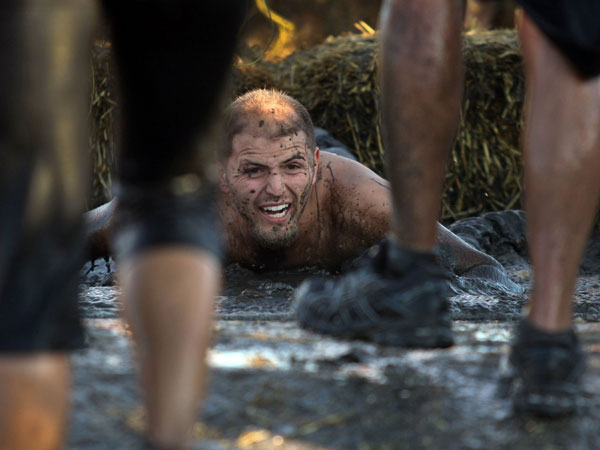 A Tough Mudder runner lands in the mud after being shocked as he runs through the mud, water and straw bales in the electroshock therapy obstacle course in the hills near Temecula, California, February 25, 2012. (Allen J. Schaben/Los Angeles Times/MCT)
