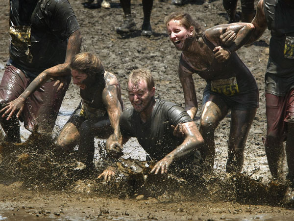 Part of a team of runners take a tumble in the final muddy obstacle near the end of the 10K race course at the 20th annual Marine Corps´ World Famous Mud Run at Camp Pendleton, June 1, 2013. (Don Bartletti/Los Angeles Times/MCT)
