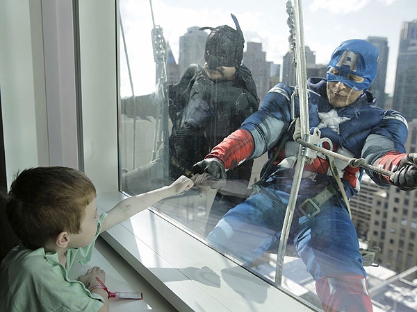 Window washers Pedro Castro, 45, as Batman, and Roberto Duran, 32, as Captain America, right, entertain patient Zakk Carrier, 5, as they hang from rope lines from the roof of the Ann & Robert H. Lurie Children´s Hospital to entertain children in what has become a beloved semi-annual tradition, April 15, 2014, in Chicago. (Michael Tercha/Chicago Tribune/MCT)