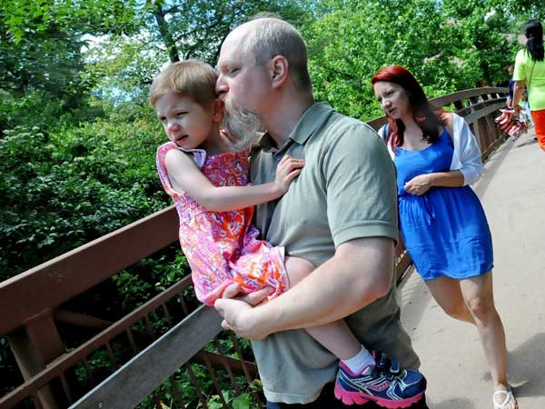 Sandy Edelman gives a kiss to his daughter, Angelina Phillips-Edelman, 4, who has been diagnosed with neuroblastoma, as they walk through Van Saun Park in Paramus, N.J.
