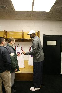 Sixers Alum Moses Malone hands a fan an autograph in the Sixers locker room at the Spectrum.