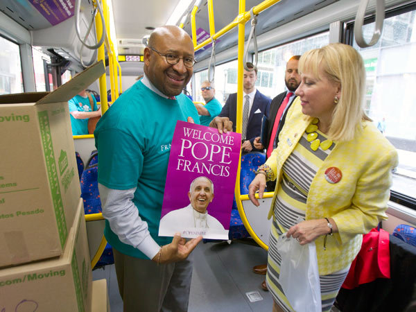 """Mayor Michael Nutter, left, and Donna Crilley Farrell, executive director of the World Meeting of Families, show the poster from an """"OpeninPHL"""" kit. (CHARLES FOX/Staff Photographer)"""