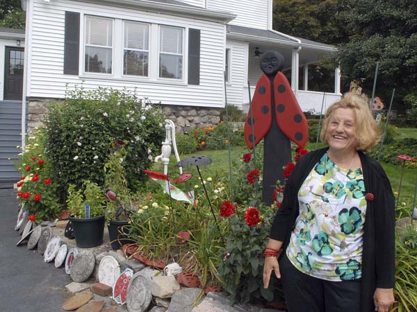 In this Aug. 26, 2013 photo, Sue Pace stands in front of her home in Stamford, Conn. She collects almost anything to do with ladybugs. (AP Photo/Stamford Advocate, Dru Nadler)