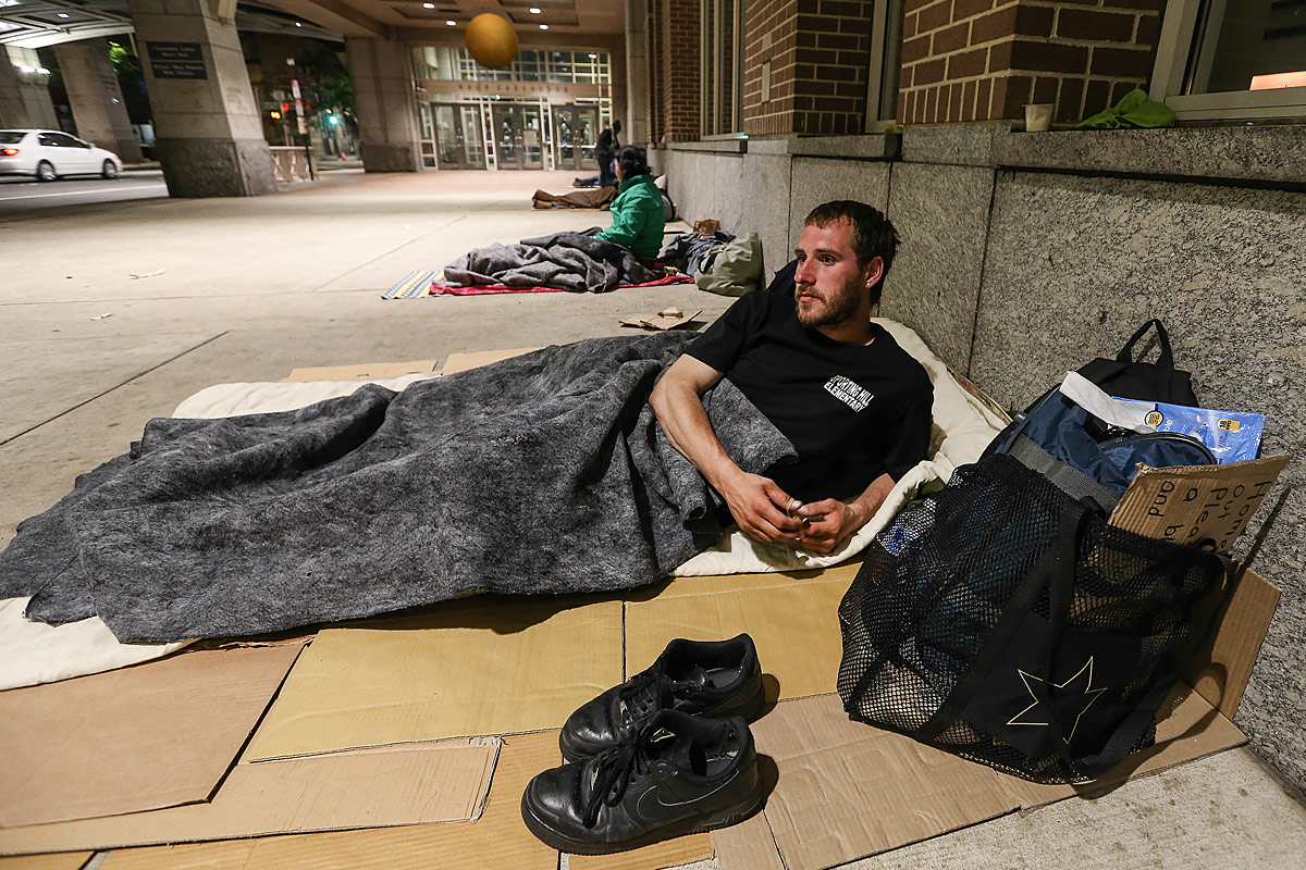 Matt, 28, of Montgomery County, gets ready for bed under the Pennsylvania Convention Center.