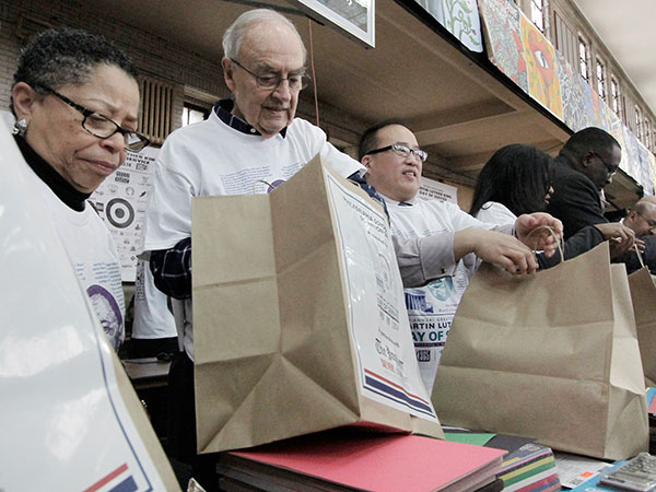 (Left to right) Volunteers Sharmain Matlock-Turner, Pres of Urban Affairs Coalition, Senator Harris Wofford and Phila. Councilman at Large David Oh fill bags with school supplies in fast assembly line fashion during the Martin Luther King Day event and celebration at Girard College in Philadelphia on January 20, 2014. ( ELIZABETH ROBERTSON / Staff Photographer )