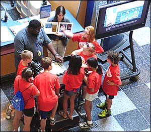 A group of children watches a demonstration at the Franklin Institute of how and why oil spills spread.