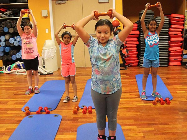 Ashley Jackson, 10, front, works out during Ricky Dickerson´s fitness class, July 14, 2014 at Memorial West Hospital in Pembroke Pines, Fla., a boot camp for kids to help them stay active and healthy. (Patrick Farrell/Miami Herald/MCT)