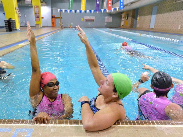 Try It For Life athlete Pam Christian, left, gets help with her backstroke from Try It For Life mentor Lisa McDaniel during a swim lesson on May 15,2014 at the Dowd YMCA in Charlotte, N.C. (Robert Lahser/Charlotte Observer/MCT)
