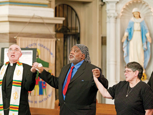 At St. Vincent De Paul Church in Germantown on Wednesday, pastor Sylvester Peterka (left), exonerated death-row inmate Harold Wilson (center), and other participants in a prayer rally against capital punishment join hands and sing after the announcement of the stay of execution for inmate Richard Glossip in Oklahoma. (CHARLES FOX/Staff Photographer)