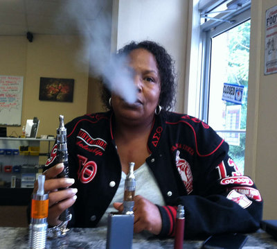 Robin Patterson of Allentown, N.J., vaping with her new variable voltage e-cigarette at Ecigs International, an e-cigarette store in Roxborough.