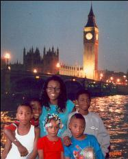 Lathenia Petty with her children in front of a poster of London