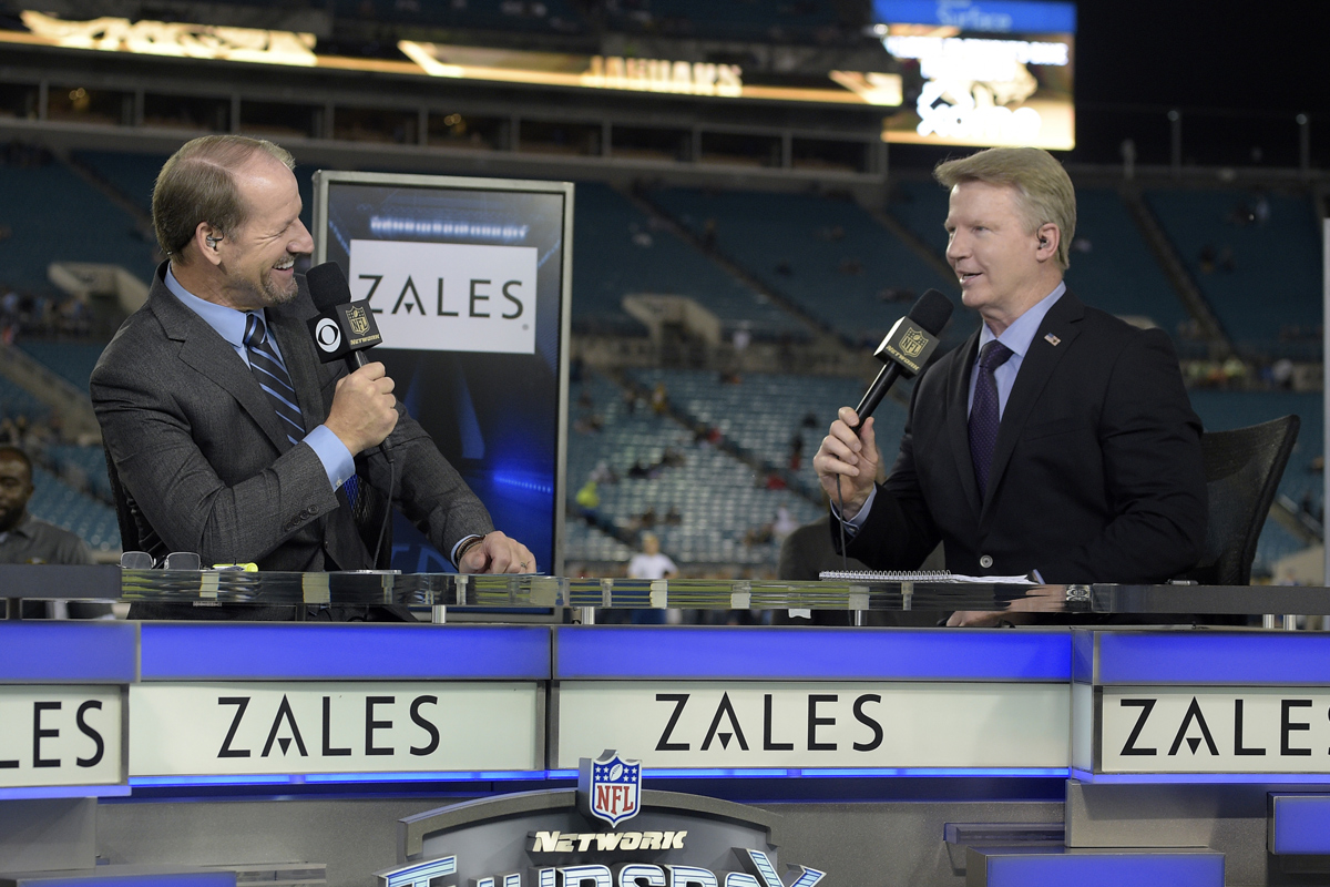 CBS Sports NFL analyst Phil Simms (right) with colleague Bill Cowher. After being replaced by Tony Romo as the network´s top analyst, Simms will join Cowher, James Brown, Boomer Esiason, and Bart Scott in the CBS studio during the NFL´s 2017 season.