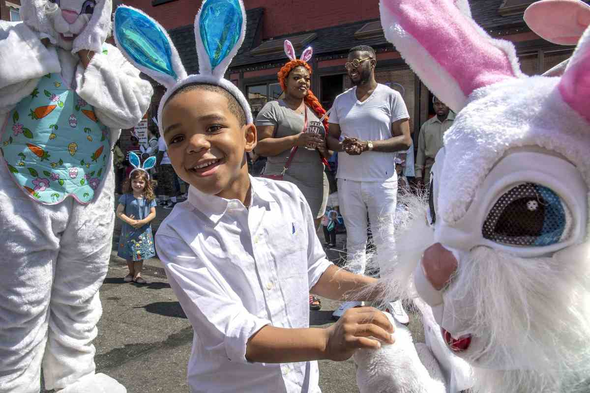 Kaeem Henderson, 4, meets with the Easter Bunnies before the start of the 86th annual Easter Promenade down South Street. Kaeem and his parents, Diana Chambers and Malik Clemons (rear), are from Juniata.