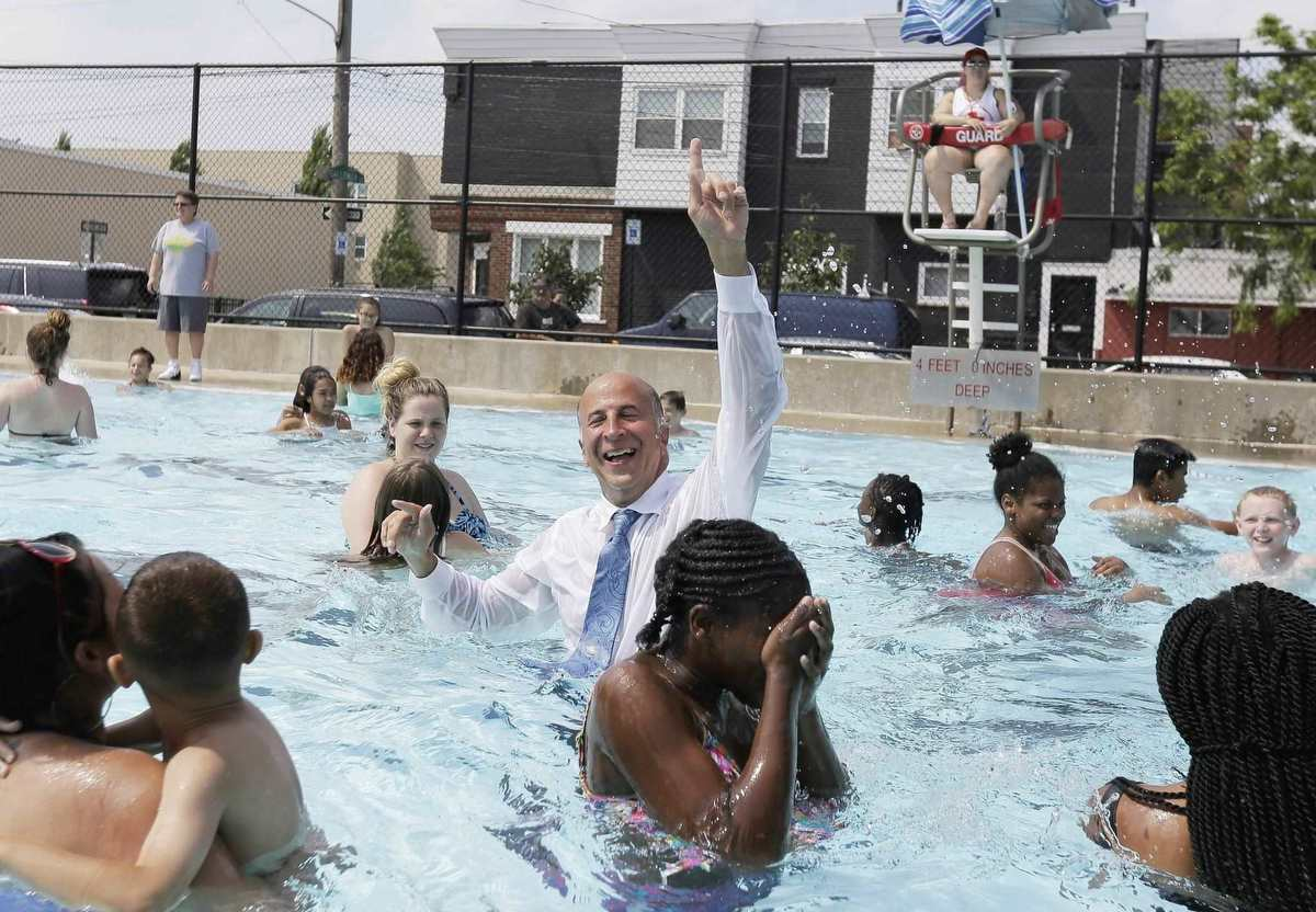 Councilman Mark Squilla surprises everyone by jumping into the pool at the Murphy Recreation Center in South Philadelphia Thursday June 22, 2017. following a dedication ceremony for new playground equipment at the center and announcing the official opening of public pools for the 2017 summer season.